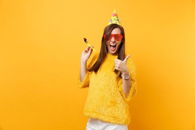 Fröhliche frau in orange lustiger brille, geburtstagshut mit pfeife, die daumen nach oben zeigt, isoliert auf hellgelbem hintergrund feiernd. menschen aufrichtige emotionen lifestyle-konzept. werbefläche.