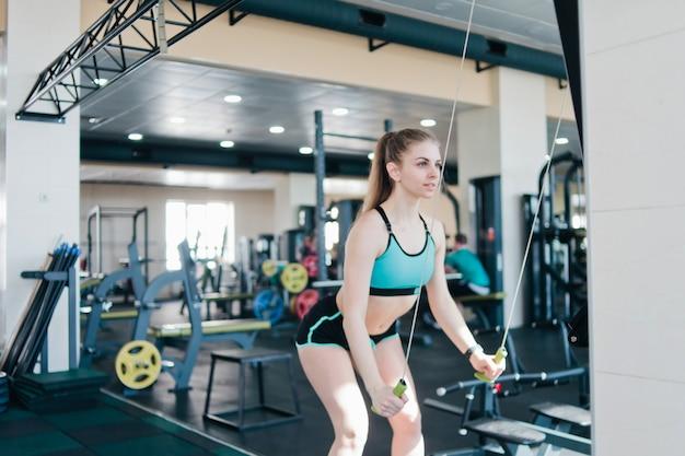 Fröhliche frau in sportbekleidung trainiert im simulationsgerät des skifahrers im fitnessstudio.