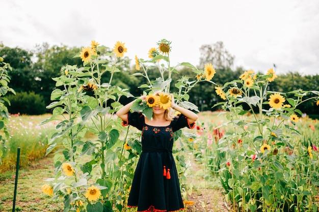 Fröhliche frau in traditioneller slawischer kleidung, die in sonnenblumen im freien aufwirft