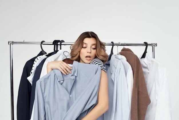 Fröhliche frau kleiderbügel kommode mode interieur studio lifestyle. foto in hoher qualität