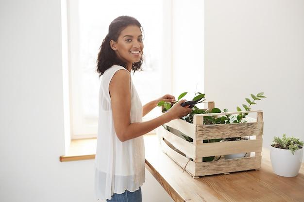 Fröhliche frau lächelnd, die vorbereitet, pflanzenstämme über weiße wand und fenster zu schneiden