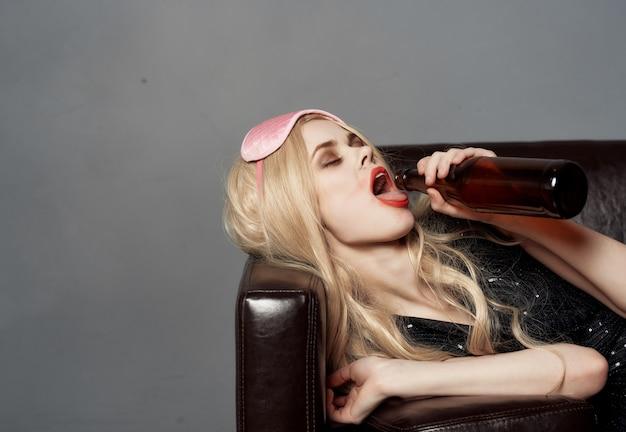 Fröhliche frau liegt auf dem sofa alkohol emotionen schlafmaske