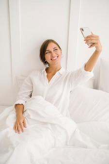 Fröhliche frau macht ein selfie auf einem weißen bett