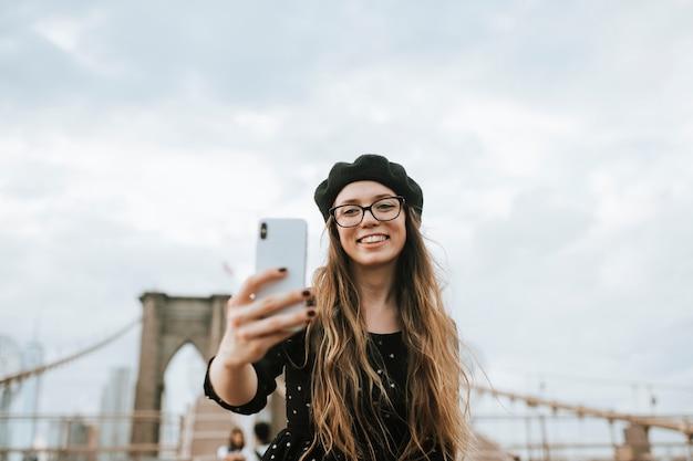Fröhliche frau macht ein selfie mit der brooklyn bridge, usa