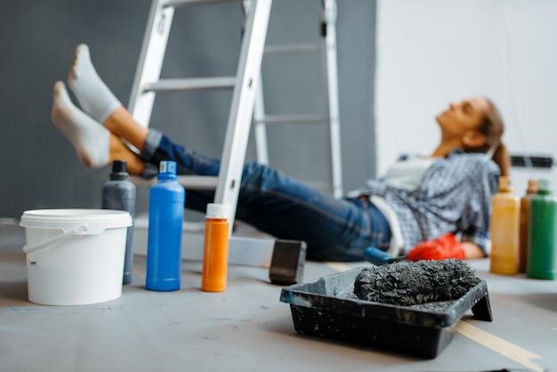 Fröhliche frau macht hausreparatur, glückliche frau, die wohnungsrenovierung macht, zimmerdekoration renoviert