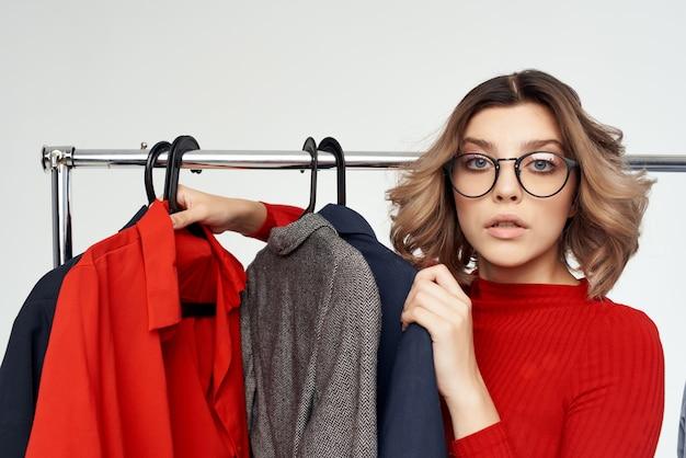Fröhliche frau mit brille, die auf bekleidungsgeschäft shopaholic hellem hintergrund anprobiert. foto in hoher qualität