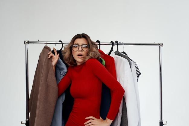 Fröhliche frau mit brille neben kleidung mode spaß hellem hintergrund. foto in hoher qualität