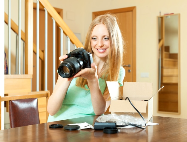 Fröhliche frau mit dem blonden haar, das zu hause für neue digitalkamera auspackt