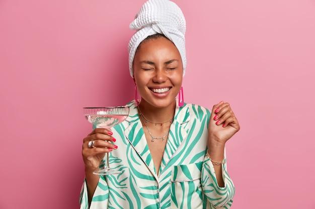 Fröhliche frau mit dunkler haut, schließt die augen und lächelt breit, genießt die freizeit zu hause, feiert die suche nach einem neuen job oder einem erfolgreichen geschäft, hält ein glas martini in der hand, gekleidet in lässige hauskleidung