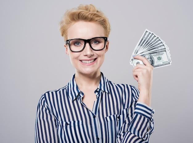 Fröhliche frau mit einem fan von geld