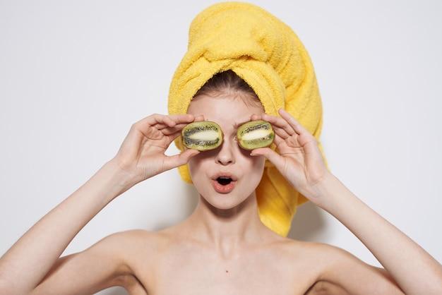 Fröhliche frau mit einem gelben handtuch auf dem kopf mit kiwi