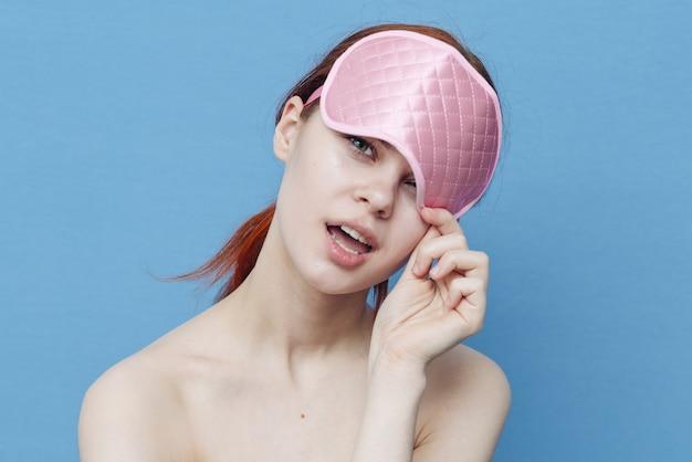 Fröhliche frau mit einer medizinischen maske auf ihrem kopf auf einem blauen hintergrund schaut zur seite