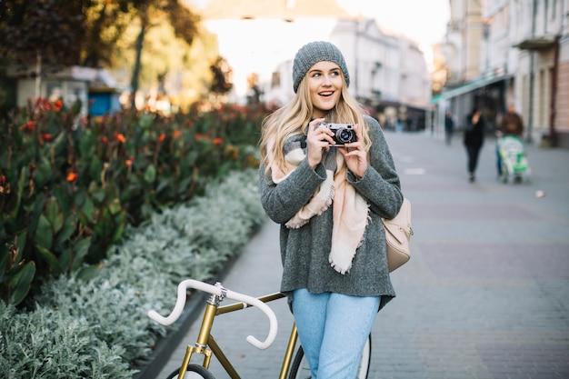Fröhliche frau mit fahrrad und kamera
