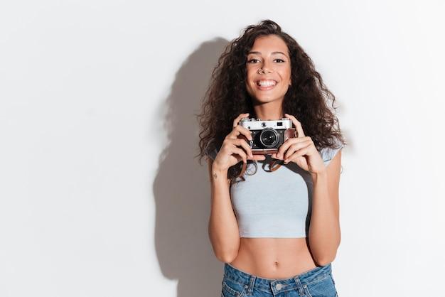 Fröhliche frau mit fotokamera suchen und lächeln