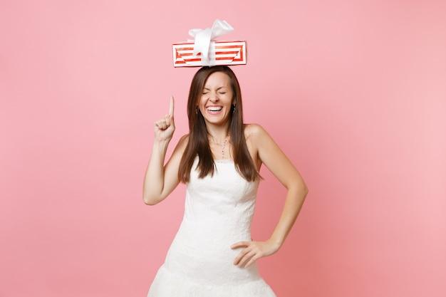 Fröhliche frau mit geschlossenen augen im weißen kleid, die mit dem zeigefinger auf die rote schachtel mit geschenk auf dem kopf zeigt
