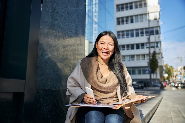 Fröhliche frau mit handy und papieren, die draußen auf stufen sitzt