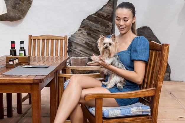 Fröhliche frau mit hund im café