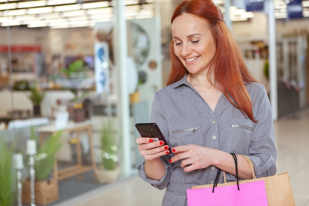 Fröhliche frau mit ihrem smartphone im einkaufszentrum, kopieren raum. attraktive kundin, die mit einkaufstüten im einkaufszentrum geht und online auf ihrem telefon surft