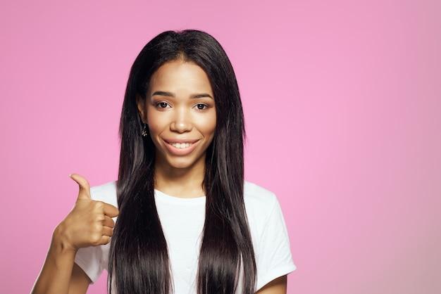 Fröhliche frau mit langen schwarzen haaren in einem weißen t-shirt frisur kosmetik rosa hintergrund