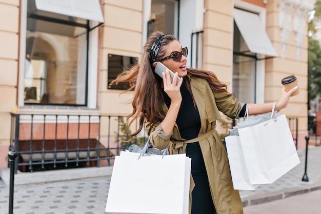 Fröhliche frau mit langer frisur, die am telefon spricht und sich beim einkaufen umsieht