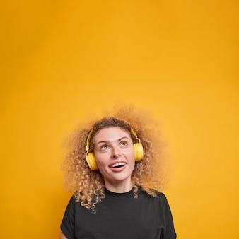 Fröhliche frau mit lockigen, buschigen haaren schaut glücklich nach oben und trägt neugierig stereo-kopfhörer in schwarzem t-shirt, isoliert über gelber wand. menschen- und freizeitkonzept