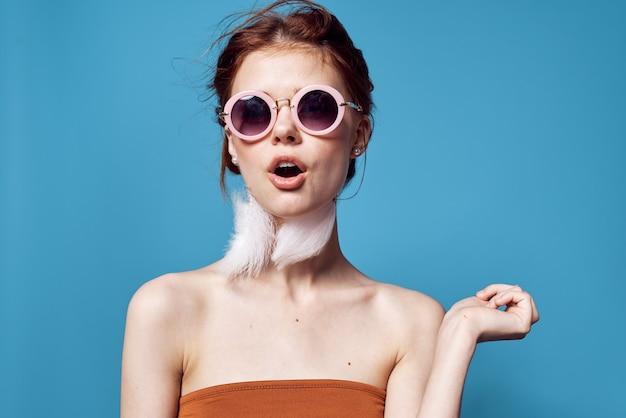 Fröhliche frau mit nackten schultern sonnenbrillen modeschmuck