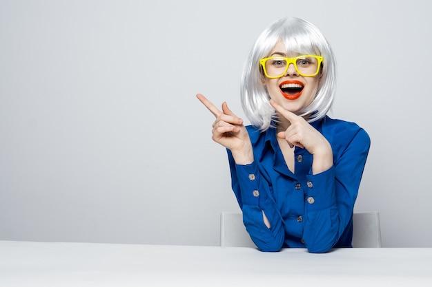 Fröhliche frau mit roten lippen in einer weißen perücke, die mit ihren händen gelbes glamour-glamourmodell gestikuliert