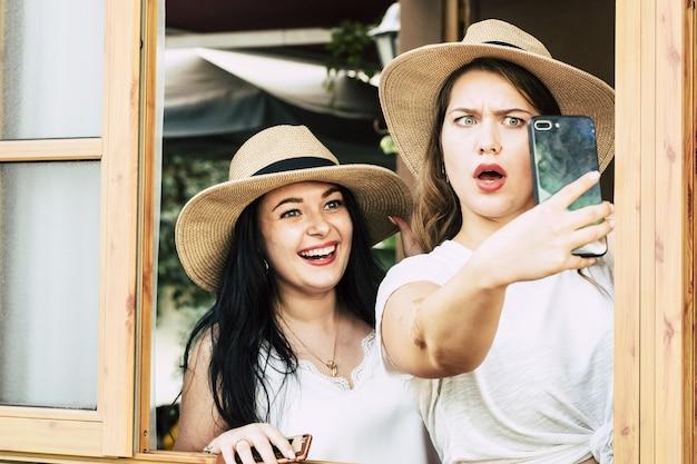 Fröhliche frau mit schockierter freundin, die selfie mit handykamera macht. zwei schöne freundinnen mit strohhut machen selfie mit handykamera durch offenen fensterrahmen