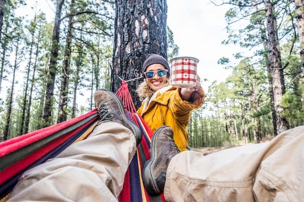Fröhliche frau mit tasse kaffee genießen sie die natur, entspannen sie sich bei der freizeitgestaltung im freien mit einem mann, der auf der hängematte liegt - glückliche menschen in waldwäldern freiheit lebensstil zusammen - reisen und umwelt