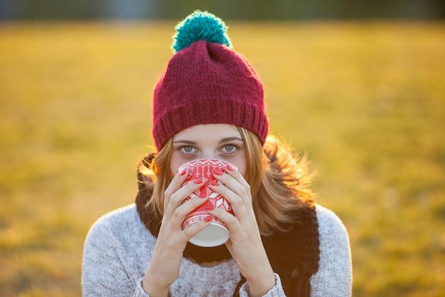 Fröhliche frau mit warmem hut, der kaffee trinkt