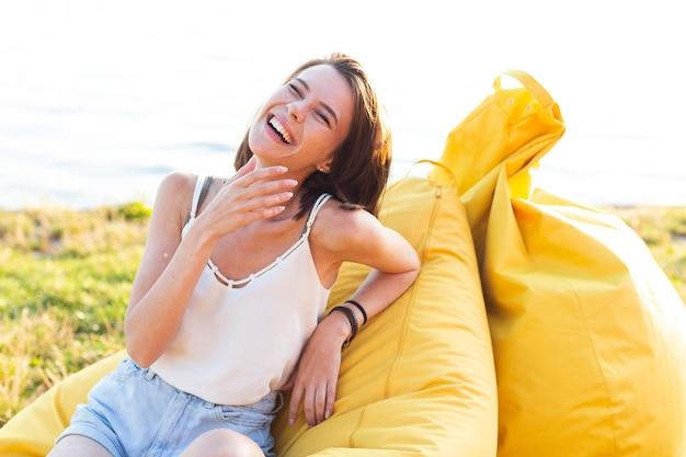 Fröhliche frau posiert auf gelben sitzsack