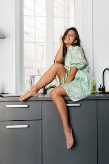 Fröhliche frau sitzt auf arbeitsplatte in der modernen küche.