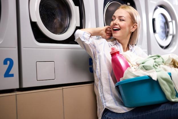Fröhliche frau sitzt glücklich und wartet auf das ende der wäsche, lächelt und hält das becken mit schmutziger kleidung und rosa waschmittelflasche