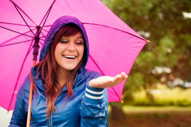 Fröhliche frau unter rosa regenschirm, der für regen prüft
