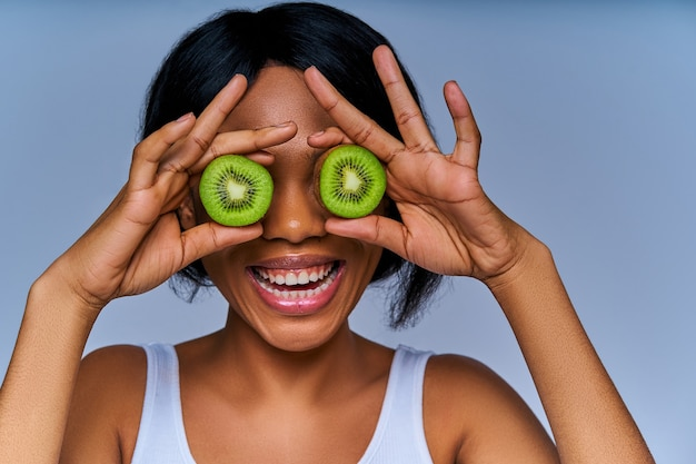 Fröhliche frau versteckt ihre augen hinter hälften der grünen kiwi. diätkonzept