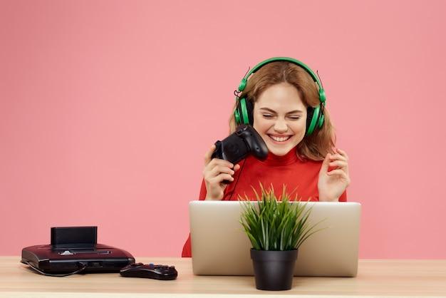 Fröhliche frau vor laptop mit kopfhörern, die unterhaltung spielen
