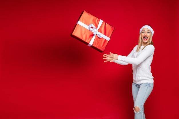 Fröhliche frau werfen eine große kiste mit einem weihnachtsgeschenk auf