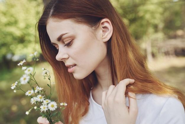 Fröhliche frau wildblumen natur sun freiheitsreise. foto in hoher qualität