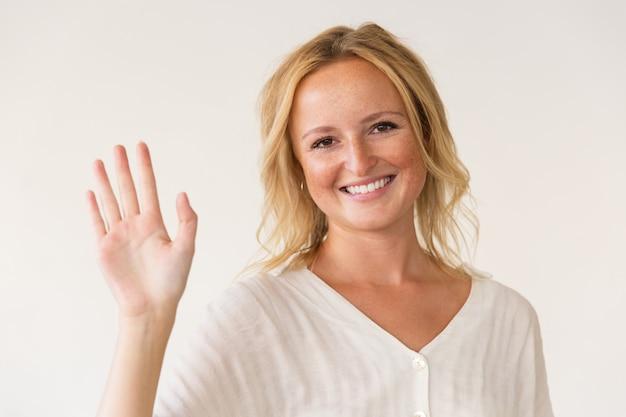 Fröhliche frau winkt hand