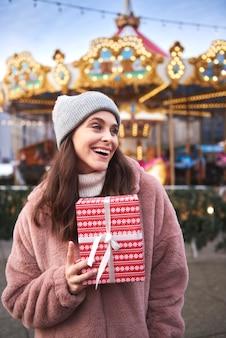 Fröhliche frauen mit geschenk auf dem weihnachtsmarkt