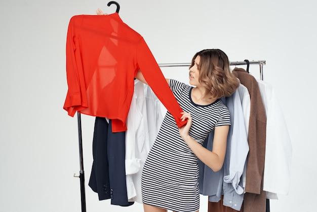 Fröhliche frauenauswahl an kleidung in der nähe des hellen hintergrunds der garderobe
