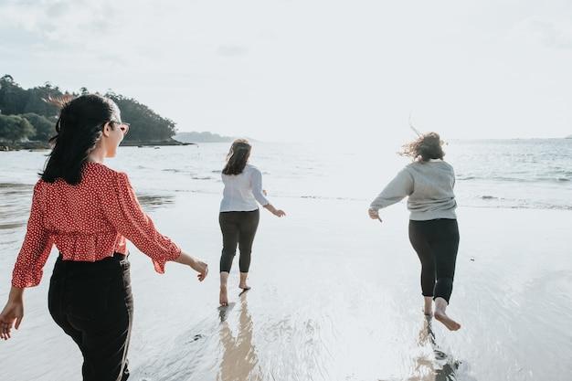 Fröhliche frauenfreunde laufen an einem hellen tag am strand, freunde entspannen sich glücklich und haben spaß beim spielen am strand in der nähe des meeres bei sonnenuntergang.