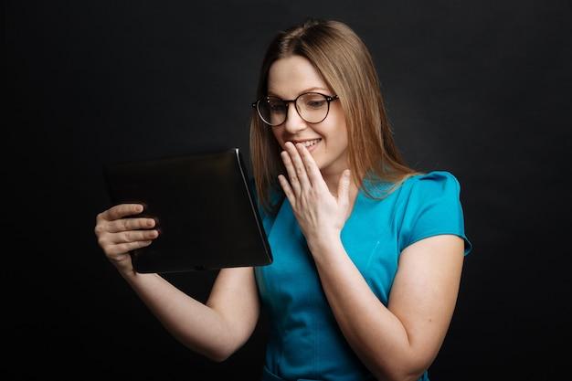 Fröhliche freudige junge frau, die lächelt und entzücken ausdrückt, während sie gadget benutzt, das isoliert in der schwarzen wand steht