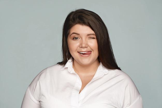 Fröhliche freudige mollige übergewichtige frau im formellen weißen hemd, die spaß im büro während der pause hat, zwinkert und zunge herausstreckt, flirtet oder sie neckt