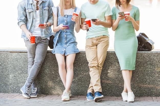 Fröhliche freunde, die am handy tippen. junge leute, die das smartphone betrachten. gruppe von freunden im freien mit handys und kaffee.