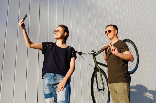 Fröhliche freunde, die zusammen spaß haben. hübsche frau nimmt ein selfie auf dem smartphone, steht mit glücklichem kerl, hält ein fahrrad auf seiner schulter und zeigt friedenszeichen. draußen.
