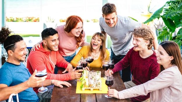 Fröhliche freunde, die zusammen spaß haben, wein auf dem dach auf einer privaten hausparty zu trinken?