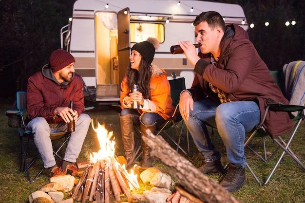 Fröhliche freunde lachen und trinken bier auf einem campingplatz am lagerfeuer. retro-wohnmobil.