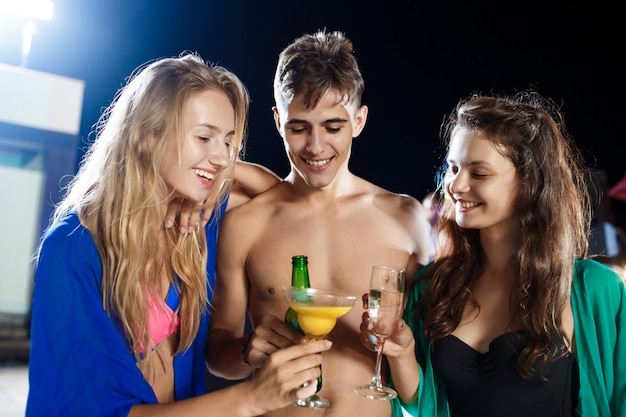 Fröhliche freunde lächeln, freuen sich, ruhen sich auf der party in der nähe des schwimmbades aus