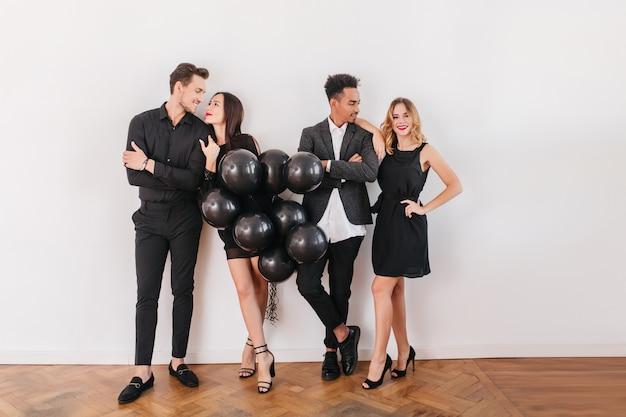 Fröhliche freunde mit schwarzen luftballons während der hausparty
